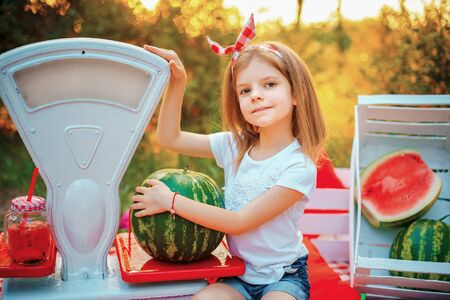 A little girl in a white T-shirt and red headband sits on a rug in nature and holds a watermelon, which stands on an old-fashioned scales. Sales concept. Stock Photo