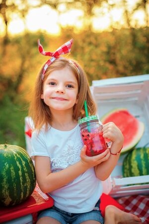 Child drinking Watermelon lemonade in jar with ice and mint as summer refreshing drink. Cold soft drinks with fruit.