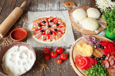 Cook in the kitchen putting the ingredients on the pizza. Pizza concept. Production and delivery of food. 写真素材