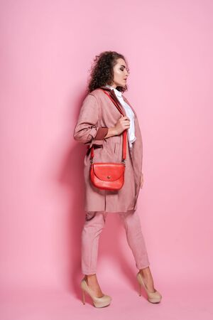Young elegant woman in trendy pink coat. isolated studio shot.