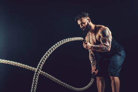 Bearded men with rope in functional training. Studio shot, isolate. Archivio Fotografico