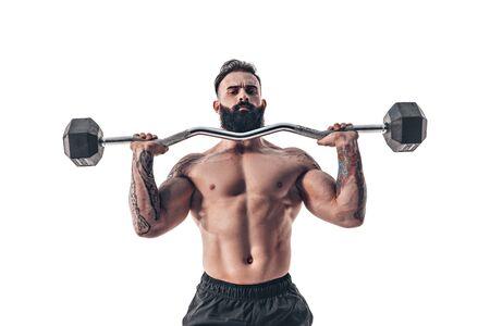 Muscular bodybuilder guy doing exercises with dumbbell over white background. Stock Photo