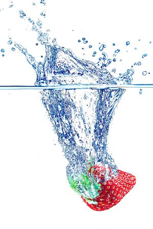 A strawberry splashing into water Isolated on white background.