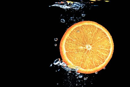 orange in water on a black background under water with bubbles. Stok Fotoğraf