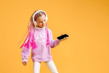 Pretty modern girl with pink dreadlocks in headphones smiling and making selfie on smartphone isolated over yellow.