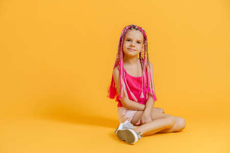 Stylish girl with pink dreadlocks sitting, looking at camera and posing on a yellow background. Beauty, fashion.