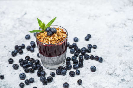Healthy breakfast or morning snack with chia seeds pudding, granola, muesli and blueberries on white stone background, vegetarian food, diet and health concept.