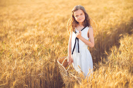 Fashion photo of a little girl in white dress and straw hat at the evening wheat field.