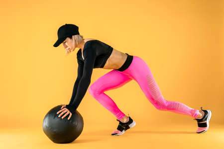 Woman in fitness clothes training with a medicine ball. Female athlete doing abdomen workout using a medicine ball. Yellow background, studio shot, isolate. Reklamní fotografie