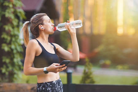 Young woman drinking water after running and using smart phone on the green park background.