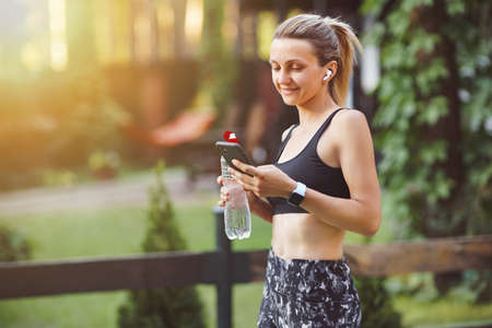 Young woman checking smart phone after workout on the green park background.