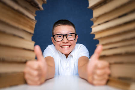 Happy smart boy in glasses sitting between two piles of books and look at camera smiling, showing thumbs up.