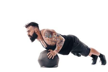 one caucasian man exercising fitness weights Medicine Ball push ups exercises in studio isolated on white background. Standard-Bild