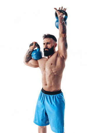 Muscular shirtless tattooed bearded male athlete bodybuilder workout with kettlebell on a white background. Isolate