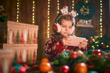 Girl using phone near Christmas tree in the decorative interior. Christmas and New Year photo. Archivio Fotografico
