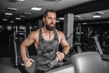 Adult strong bearded man running on treadmill in gym. Zdjęcie Seryjne