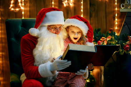 Santa Claus open and read magic book with little cute amazed girl in pajama, shallow depth of field.