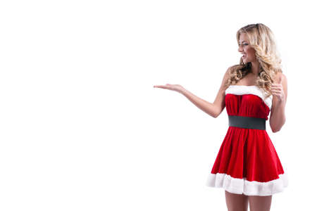 Portrait of a cheerful young blonde woman in red santa claus dress posing over white background. 写真素材
