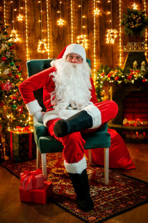 Santa sitting at the Christmas tree, near fireplace and looking at camera. Indoors. Stock Photo