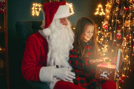 Santa Claus with a little cute girl open magical gift box in the room. Christmas time.