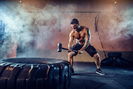 Sports training for endurance, man hits big tire hammer. Concept workout.