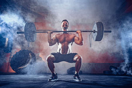 Muscular fitness man doing deadlift a barbell over his head in modern fitness center. Functional training. Snatch exercise. Smoke on background.