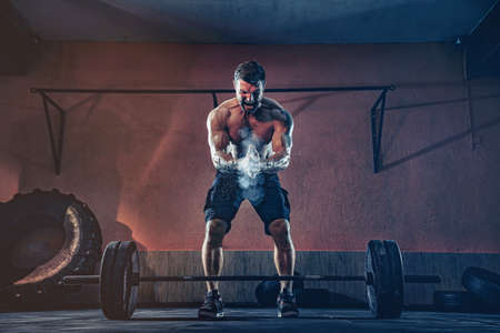 Muscular fitness man preparing to deadlift a barbell over his head in modern fitness center. Functional training. Snatch exercise.