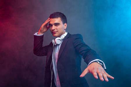 Portrait of man with headphones on dark background with smoke. Studio shoot.