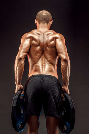 Muscled shirtless male model showing his back muscles on dark background isolate. Archivio Fotografico