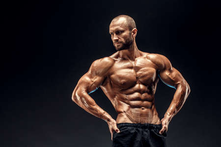 Strong man with perfect abs, shoulders, biceps, triceps and chest. Bodybuilder flexing his muscles over black background. Imagens