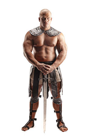 Severe barbarian in leather costume with sword. Portrait of balded muscular gladiator. Studio shot. Isolated on white background.
