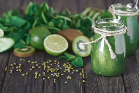 Blended green smoothie with ingredients on the stone board, wooden table selective focus