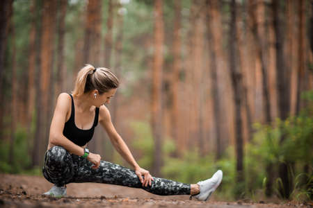 Young woman jogging outside in a pine forest. Young woman doing workout in forest. Natural forest light.