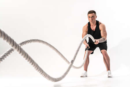 Attractive muscular man working out with heavy ropes. Photo of handsome man in sportswear isolated on white background. Crossfit
