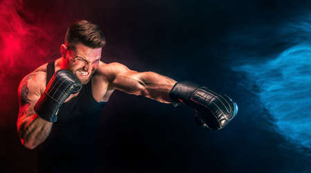 Bearded tattooed sportsman muay thai boxer in black undershirt and boxing gloves fighting on dark background with smoke. Sport concept. Stock Photo