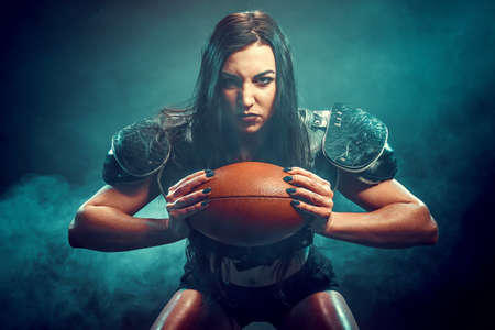 Young brunette wearing uniform of rugby football player posing with ball.