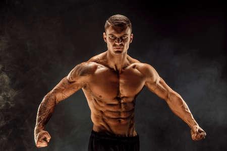 Very brawny guy bodybuilder posing. Beautiful sporty guy male power. Fitness muscled man. Roar.