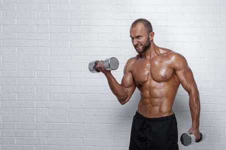 Bodybuilder doing exercises for biceps with a dumbbells against brick wall.