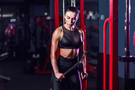 Fit well-trained woman workout triceps lifting weights in gym. Athletic woman doing exercise using machine in gym - side view.