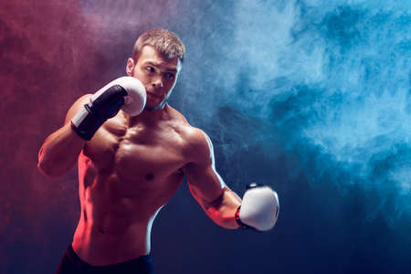 shirtless boxer with gloves on dark background. Isolate