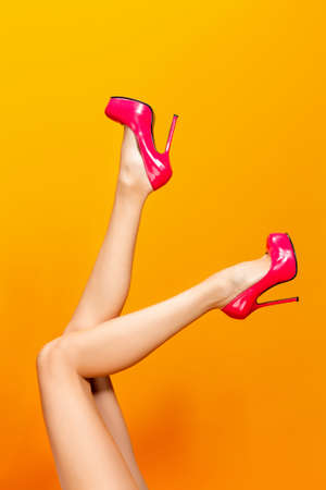 Female legs wearing pink summer high heels over yellow background