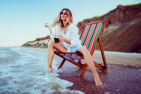 Pretty blonde woman in the shape of a heart sunglasses, white shirt and stripped swimsuit relaxing on a lounger beach and drinks coctail. summer vacation concept. Reklamní fotografie