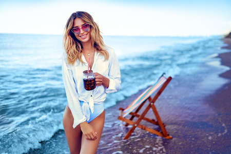 Pretty blonde woman in the shape of a heart sunglasses, white shirt and stripped swimsuit relaxing on beach and drinks coctail. summer vacation concept.