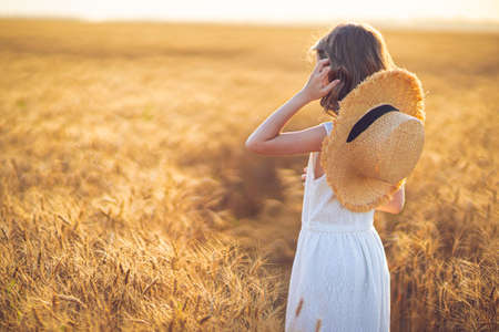 Little girl walking in sunset wheat field Banque d'images