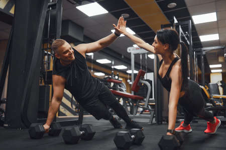 Strong and Beautiful Athletic Fitness Couple in Workout Clothes Doing Push Up Exercises and Giving Each Other a High Five