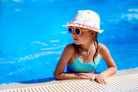 Happy girl in Sunglasses and hat in outdoor swimming pool of lux