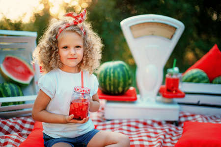 Child drinking Watermelon lemonade in jar with ice and mint