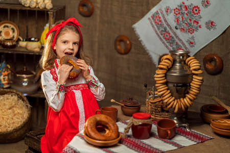 Adorable girl sitting at table full of food and big samovar. Tra Stock fotó