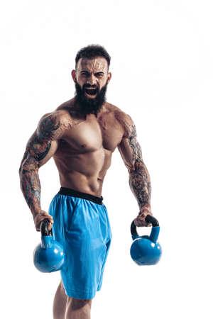 Muscular bodybuilder guy doing exercises with kettlebells over white background