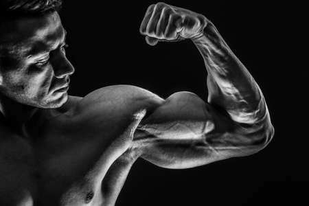 Strong Athletic Sexy Muscular Man on Black Background showing biceps Фото со стока